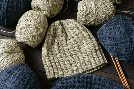 woollen: Handmade gift for couple on wintertime, woollen hat in black and beige color, woman hand knitting from ball of yarn, wool hat will keep warm in cold winter day