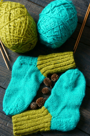 woollen: Pair of socks for winter season, knit from vibrant woollen for kid, keep foot in warm on cold day, handmade stockings, woman hand knitting with love Stock Photo