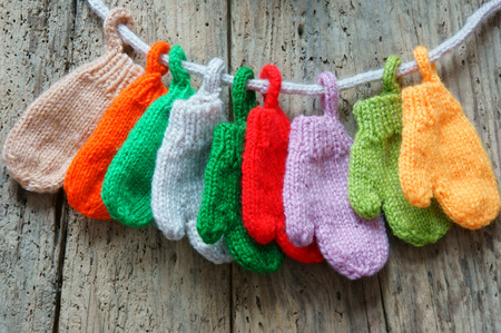 Christmas ornament for winter holiday, colorful mitten to decoration on Xmas, handmade glove hand by knitted from ball of wool