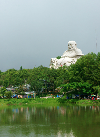 nui: Spiritual travel at Mekong Delta, Nui Cam nature reserve, ecotourism area, temple reflect on water , big buddha at high mountain, An giang, Vietnam Stock Photo