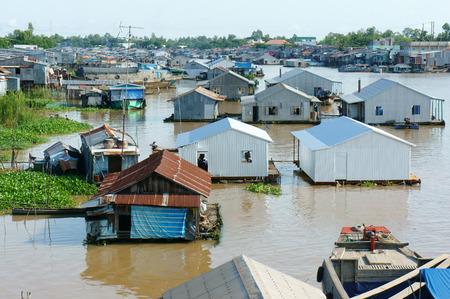 precarious: HONG NGU- VIET NAM- OCT 15: Residential on water, group of floating house of poor people on Mekong Delta river, precarious life, danger, home from sheet metal, Hongngu, Vietnam, Oct 15, 2015