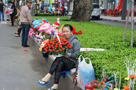 street vendor: HO CHI MINH CITY, VIET NAM- OCT 20: Vietnamese street vendor at outdoor market, woman sell colorful bouquet of flower and gift on roadside in  woman holiday, Saigon, Vietnam, Oct 20, 2014