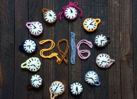 happy moment: Handmade design from yarn, group of colorful clock with many time zone to happy new year 2016, eve moment, amazing with knitted product on wooden background