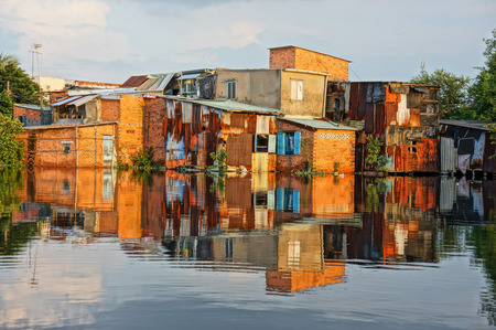 downgrade: HO CHI MINH CITY, VIET NAM- OCT 10: Group of riverside downgrade house with red brick wall, poor residence near canal, danger and  unsafe life in climate change situation, Vietnam, Oct 10, 2014
