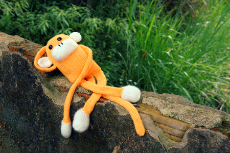 lie down: Abstract knitted monkey, symbol of year 2016, handmade toy from yarn, she lie down or sit lonely among nature, happy new year 2016, year of the monkey