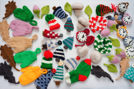 Handmade product for winter holiday, group of knitting ornament as leaf, acord, clock, mushroom, strawberry, pine tree, hat, mitten, scarf, acorn for Christmas decoration