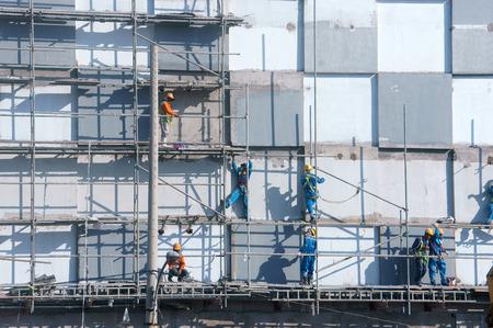 unsafe: HO CHI MINH CITY, VIET NAM- NOV17: Group of Asian construction worker working on scraffold at apartment building site, Vietnamese man climbing, danger, unsafe for builder, Saigon, Vietnam, Nov17, 2015