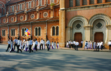 traditional dress: HO CHI MINH CITY, VIET NAM- NOV 24: Crowd of Vietnamese student in traditional dress, ao dai, shooting for yearbook at Saigon Notre Dame Cathedral, Vietnam, Nov 24, 2015