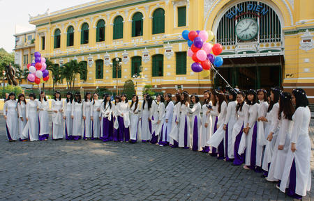 yearbook: HO CHI MINH CITY, VIET NAM- NOV 24: Crowd of Vietnamese student in traditional dress, ao dai, shooting for yearbook at Saigon central post office, Vietnam, Nov 24, 2015