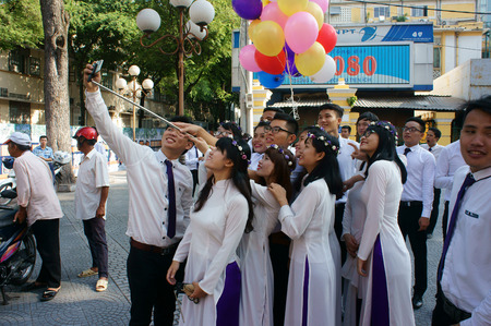 yearbook: HO CHI MINH CITY, VIET NAM- NOV 24: Crowd of Vietnamese student in traditional dress, ao dai, shooting for yearbook at Saigon Notre Dame Cathedral, Vietnam, Nov 24, 2015