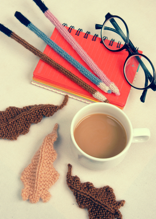 handbook: Romantic desk with ornament from handmade product, lily flower knit from white yarn, handbook, knitting pencil, coffee cup, glasses, beautifil craft Stock Photo