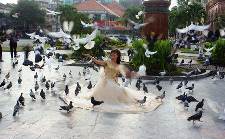 wedding photo album: HO CHI MINH CITY, VIET NAM- NOV 24: Vietnamese couple shooting for wedding photo album at Saigon central post office, beautiful bride and groom among dove, Vietnam, Nov 24, 2015