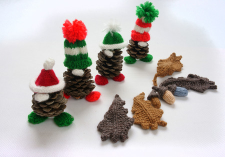 pinecone: Christmas pine gnome on white background, Xmas pinecone wear Xmas hat for decoration on winter holiday, with red, green yarn, homemade product by knitted hat, food, nose make amazing and pretty gift Stock Photo