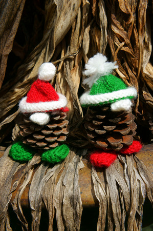 pinecone: Christmas pine gnome, Xmas pinecone wear Xmas hat for decoration on winter holiday, with red, green yarn, homemade product by knitted hat, food, nose make amazing and pretty gift Stock Photo