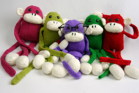 stuffed animal: Family of stuffed animal sit at new year party, group of knitted monkey in colorful yarn, symbol of 2016, funny homemade toy on white background, handmade food and calendar to happy new year