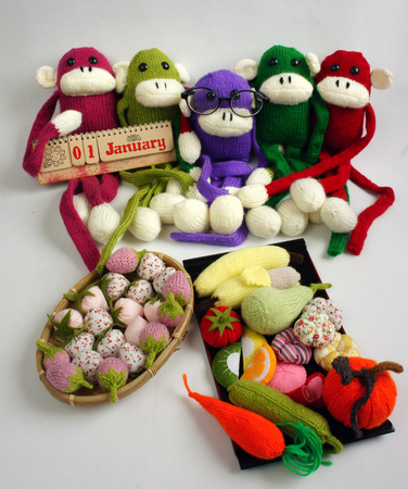 inteligent: Family of stuffed animal sit at new year party, group of knitted monkey in colorful yarn, symbol of 2016, funny homemade toy on white background, handmade food and calendar to happy new year