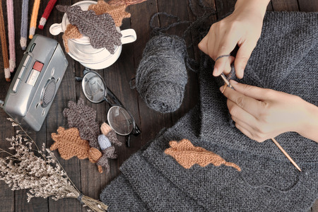 meaningful: Knitted wool scarf for winter season, meaningful handmade gift for love in wintertime, a scarf  keep warm on cold day, amazing background with glasses, coffee cup, radio, leaf in classic color