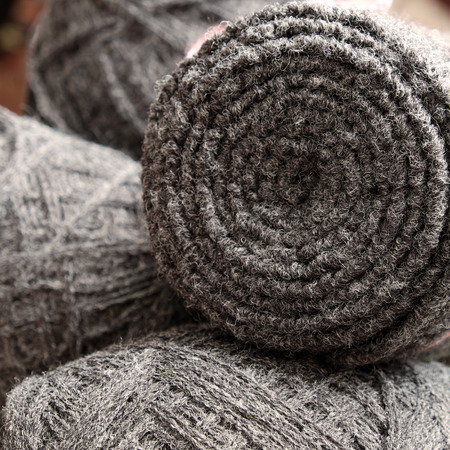 cold day: Grey scarf on wood background, a accessory in cold day of wintertime, a meaningful handmade gift, it make warm of neck, knit from dark yarn Stock Photo