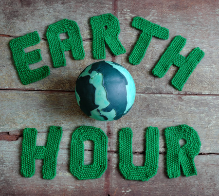 Earth hour letter in green yarn on wood background, a symbol for save the planet from climate change, handmade message for worldwide
