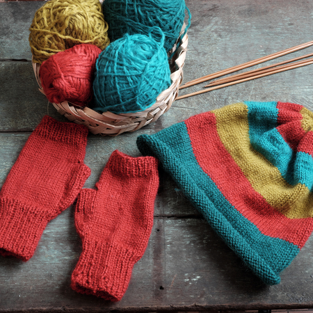 make a gift: Handmade gift for winter, knitted gloves and knit hat for cold day, group of colorful yarn make warm, knit accessories is hobby activity of woman Stock Photo