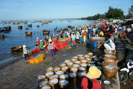 fishing scene: BINH THUAN, VIET NAM- OCT25: Crowded scene at beach in morning, group of people in fish market, purchase seafood from fisherman at fishing village, basket of anchovy, Binhthuan, Vietnam, Oct 25, 2014
