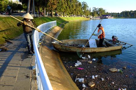 sanitation: DA LAT, VIET NAM- DEC 30: Vietnamese sanitation worker working on boat to fish rubbish out of water, trash on water make pollution, scene of Xuan Huong lake at Dalat, Vietnam, Dec 30, 2015 Editorial