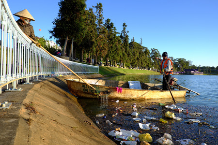 water sanitation: DA LAT, VIET NAM- DEC 30: Vietnamese sanitation worker working on boat to fish rubbish out of water, trash on water make pollution, scene of Xuan Huong lake at Dalat, Vietnam, Dec 30, 2015 Editorial