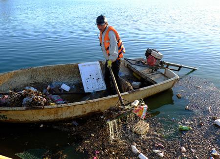 environmental sanitation: DA LAT, VIET NAM- DEC 30: Vietnamese sanitation worker working on boat to fish rubbish out of water, trash on water make pollution, scene of Xuan Huong lake at Dalat, Vietnam, Dec 30, 2015 Editorial