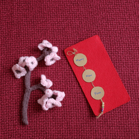 stuffed animal: 2016, year of monkey, handmade happy new year on red background, knitted monkey, funny stuffed animal, knit flower from yarn, red envelope for lucky money, sign for Vietnam Tet