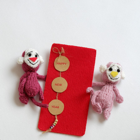 stuffed animal: 2016, year of monkey, handmade happy new year on white background, knitted monkey, funny stuffed animal, knit flower from yarn, red envelope for lucky money, sign for Vietnam Tet Stock Photo