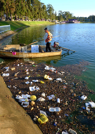 dalat: DA LAT, VIET NAM- DEC 30: Vietnamese sanitation worker working on boat to fish rubbish out of water, trash on water make pollution, scene of Xuan Huong lake at Dalat, Vietnam, Dec 30, 2015 Editorial