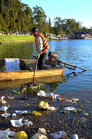 dalat: DA LAT, VIET NAM- DEC 30: Vietnamese sanitation worker working on boat to fish rubbish out of water, trash on water make pollution, scene of Xuan Huong lake at Dalat, Vietnam, Dec 30, 2015 Editorial