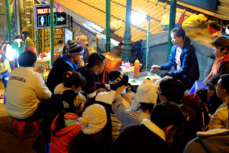 in the open air: DA LAT, VIET NAM- DEC 30: Crowded atmosphere at Dalat night market, traveler eating with street food at open air market in cold weather, light on street, crowd sit at marketplace, Vietnam, Dec 30,2015