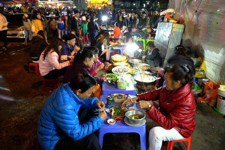 dalat: DA LAT, VIET NAM- DEC 30: Crowded atmosphere at Dalat night market, traveler eating with street food at open air market in cold weather, light on street, crowd sit at marketplace, Vietnam, Dec 30,2015