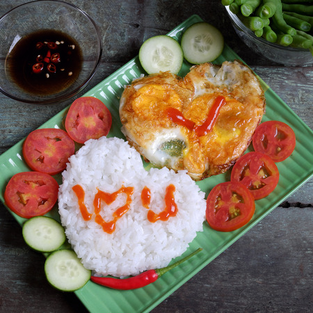 simple meal: Idea for Valentine day meal, cooked rice, omelet in heart shape, tomato, cucumber,bean for nutrition eating, simple, cheap and quick food, love you message, meaningful in love day with Vietnamese food Stock Photo