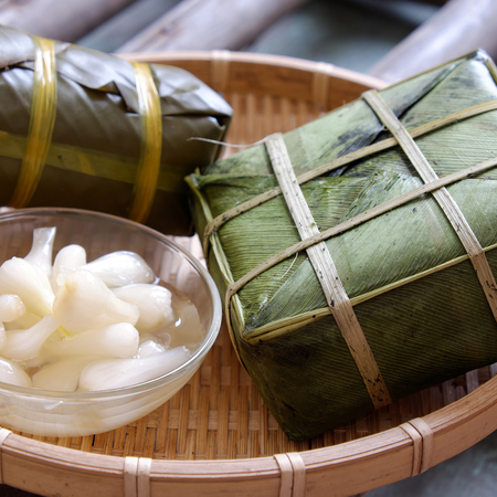 vietnamese food: Vietnamese food for Tet holiday in spring, banh chung is traditional food on lunar new year, a rice cake stuffed with pork, green bean, is tradition culture in spring Stock Photo