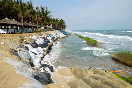 unsafe: Erosion at seaside restaurant from climate change situation, wave broken dike, very unsafe, danger, environment risk of worldwide when sea level rise by warming, scene at Cua Dai, Hoi An, Vietnam Stock Photo