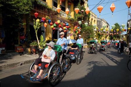 HOI AN, VIET NAM- 2016년 2월 17일 : 사람들의 그룹은 호 이안 구시 가지, 고 대 집, 국가 문화 유산, 도보, 자전거 또는 거리 륜 택시, 베트남에서 여행자의 방