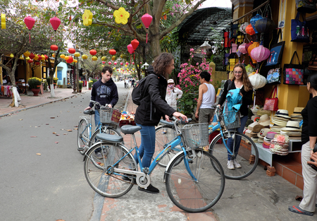 bicycle walk: HOI AN, VIET NAM- FEB 17, 2016: Group of people travel Hoian old town, ancient house, country heritage, city friendly with environment, walk, bicycle or pedicab on street, traveller visit at Vietnam