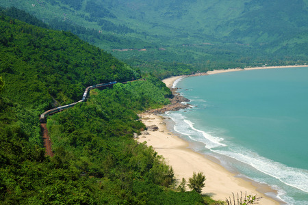 seaside: Panorama scene of Lang Co beach, Hue from Hai Van mountain pass at Da Nang, Viet Nam. Amazing landscape of train moving on railway at seaside, nice view of nature with green forest, wave on sea Stock Photo