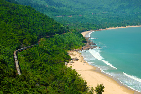 mountain pass: Panorama scene of Lang Co beach, Hue from Hai Van mountain pass at Da Nang, Viet Nam. Amazing landscape of train moving on railway at seaside, nice view of nature with green forest, wave on sea Stock Photo