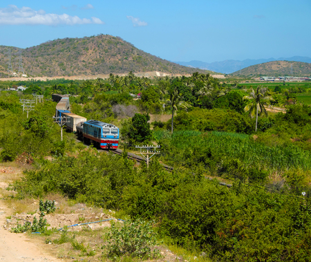 rail cross: Train moving on rail to transport passenger and good cross Binh Thuan, Viet Nam, green landscape at Binhthuan, Vietnam rural on day rural on day