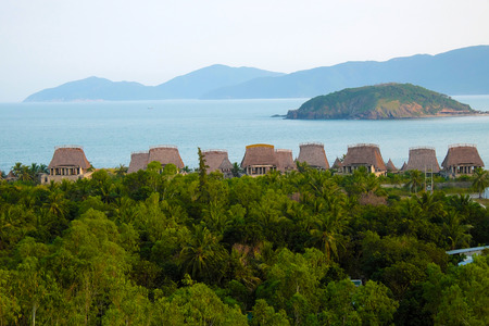 riverside landscaping: Beautiful seaside resort with group of beach bungalow, tourist area among coconut tree, sea and mountain, eco green environment, great place for holiday vacation in summer at Nha Trang, Vietnam