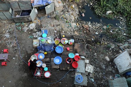 environmental sanitation: Outdoor restaurant near polluted river, area with full of rubbish, trash, pollution environment, unsafe food situation make poisoning for poor people at Ho Chi Minh city, Viet Nam Stock Photo