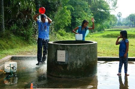 source d eau: AN GIANG, VIET nam- 20 septembre 2014: Un groupe de gens vietnamiens ont un chemin en plein air à la campagne du Vietnam, les enfants et l'homme debout à l'eau de puits pour le bain, une source d'eau à partir des eaux souterraines au delta du Mékong