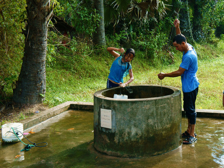 AN GIANG, VIET NAM- SEPT 20, 2014: Group of Vietnamese people have a outdoor path at Vietnam countryside, children and man stand at water well to bath, a water source from groundwater at Mekong Delta