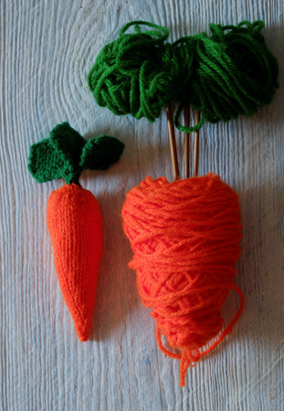 carot: Knitted carrot vegetable on wood background, funny diy by knit from yarn, orange carot with green leaf