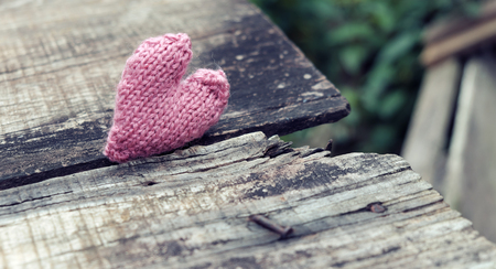 unfaithful: Lonely heart on wooden background, symbol of love with pink knitted heart in vintage color