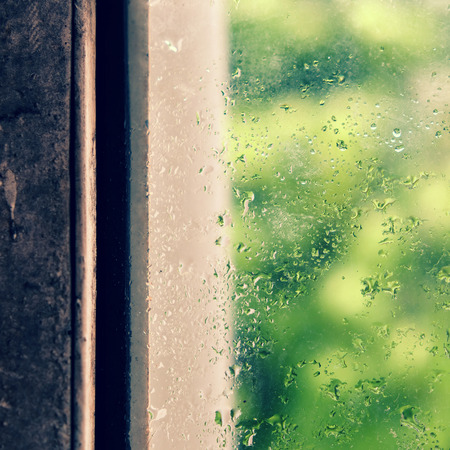 seperation: Rain drop on window in rainy day, glass with green background as seperation, nice background for love Stock Photo