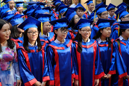 end of year: HO CHI MINH CITY, VIET NAM- JUNE 8, 2016: Group of Asian pupil in gown uniform in end year summation Editorial